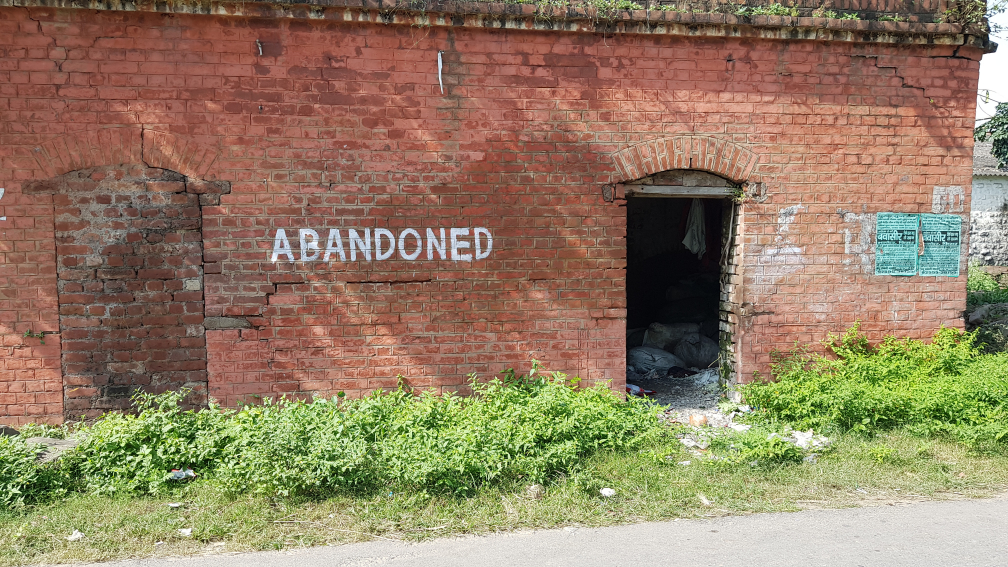 A derelict building with one doorway bricked-up and one doorway open. The word ABANDONED is painted on the wall.