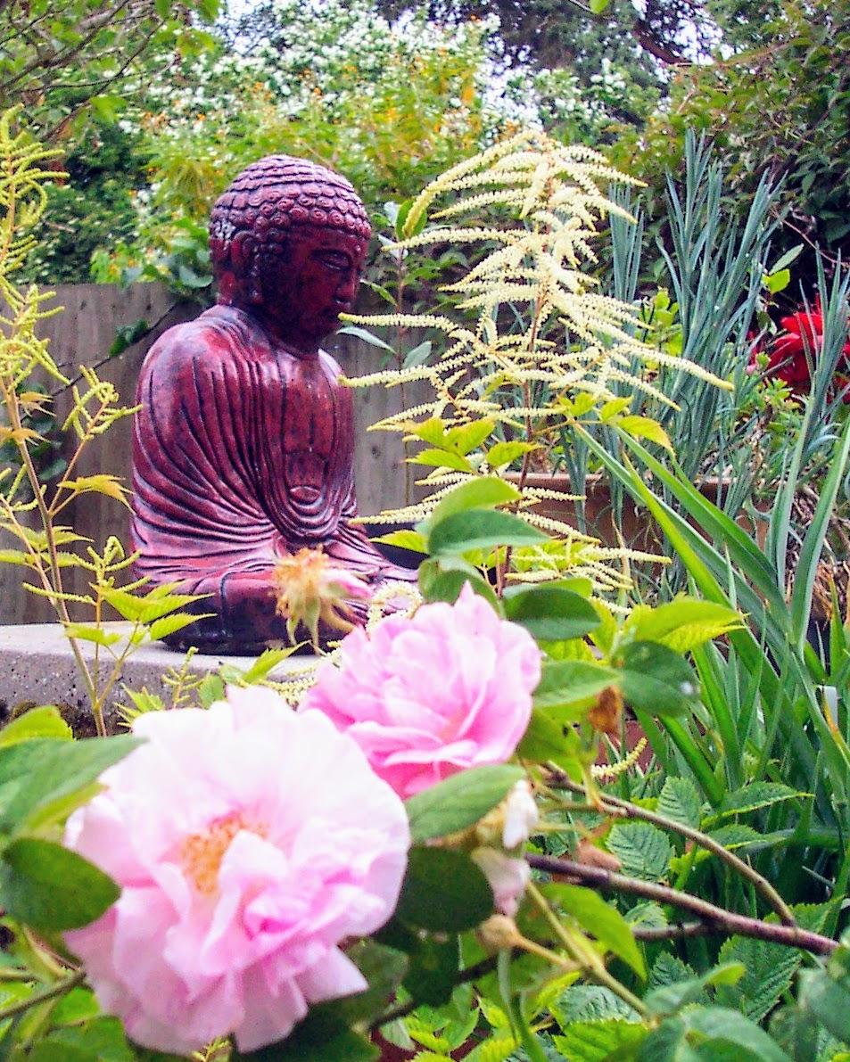 Buddha statue set amongst flowers in a garden