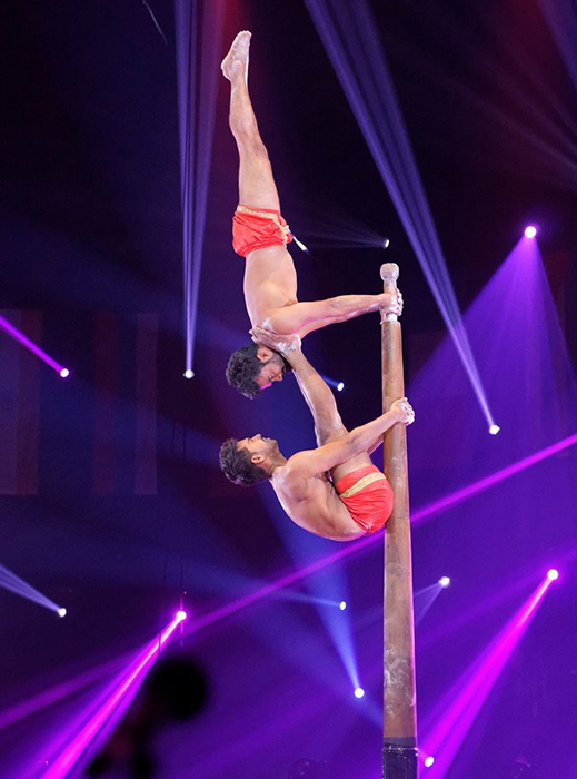 Indian acrobats supporting each other at top of pole.