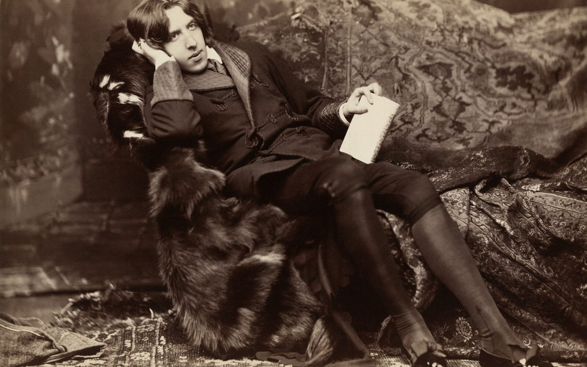 Oscar Wilde lounging on a sofa.