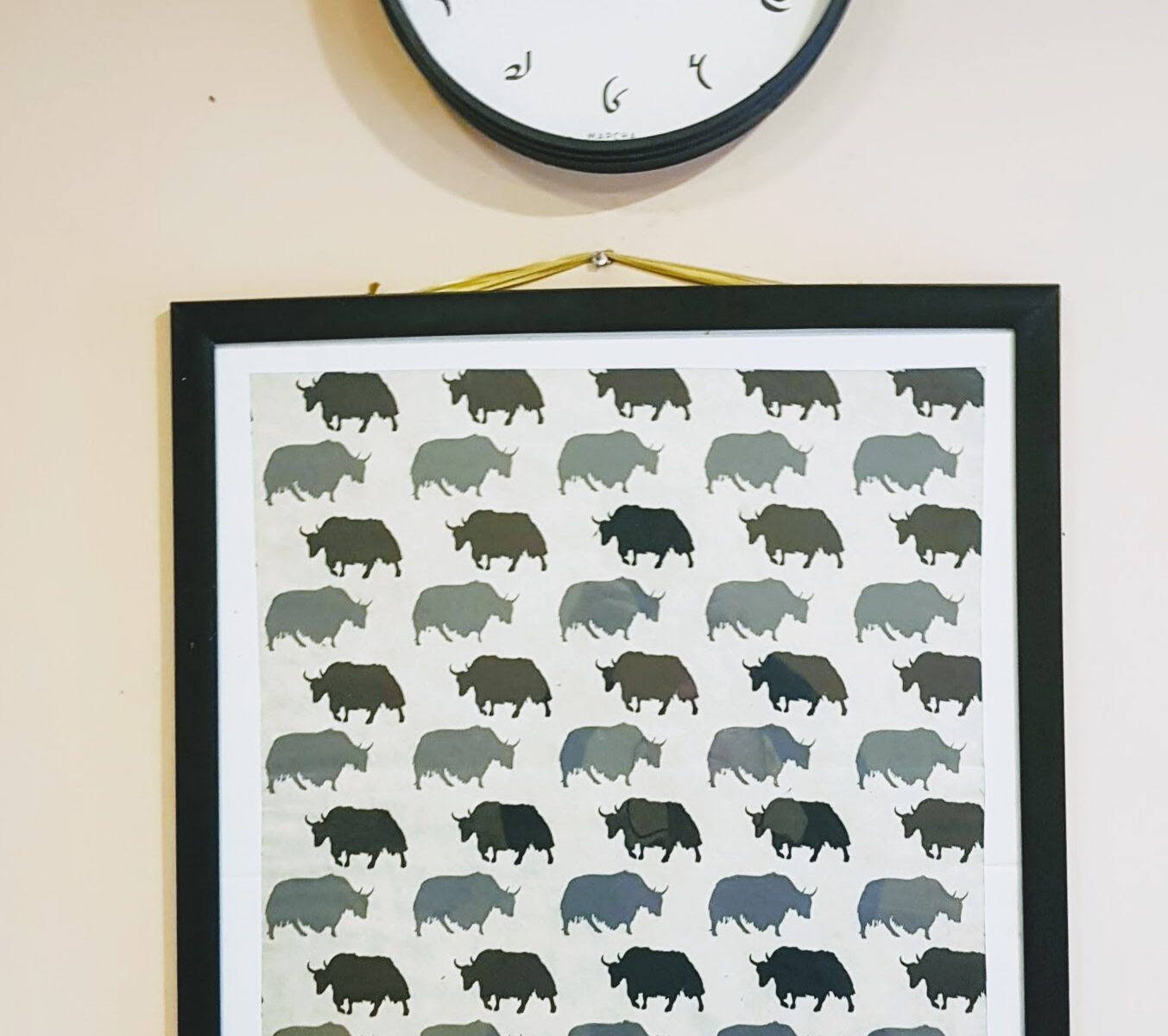 Clock with Tibetan Numerals over a black-and-white poster of Yaks going forwards and backwards.