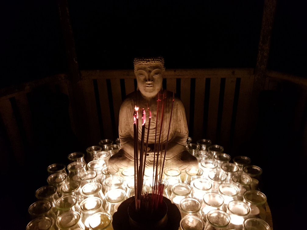 Buddha statue set amongst candles and incense.