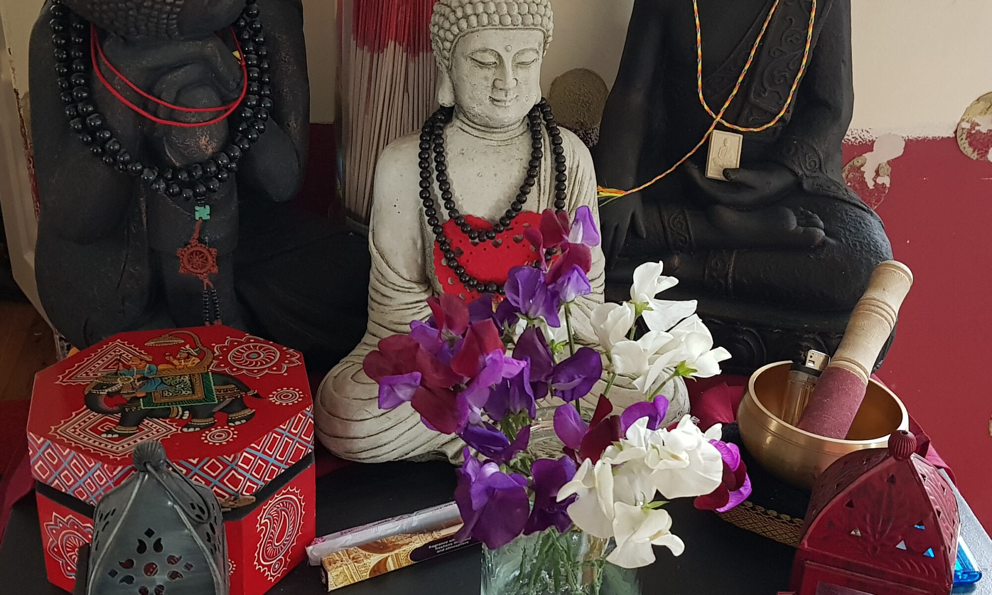 Vase of Sweet Peas in flower and Buddha figures.