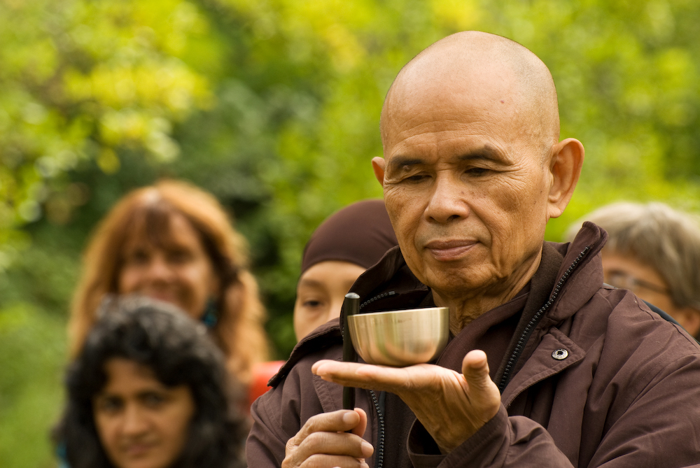 Thich Nhat Hanh 'inviting' small bell held in hand