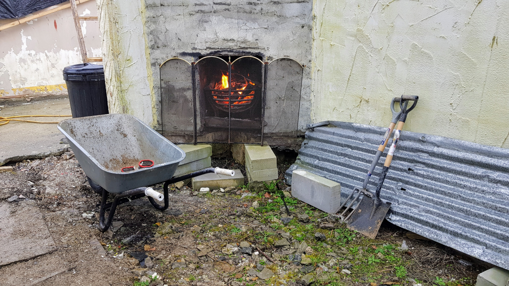 Wheelbarrow and shovel by lite fireplace in derelict building at Nalagiri House