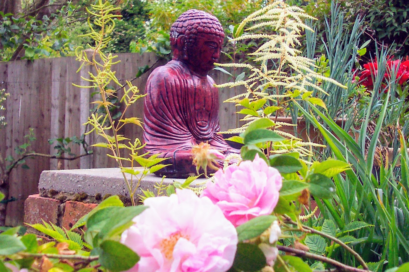 Buddha statue set amongst flowers in a garden