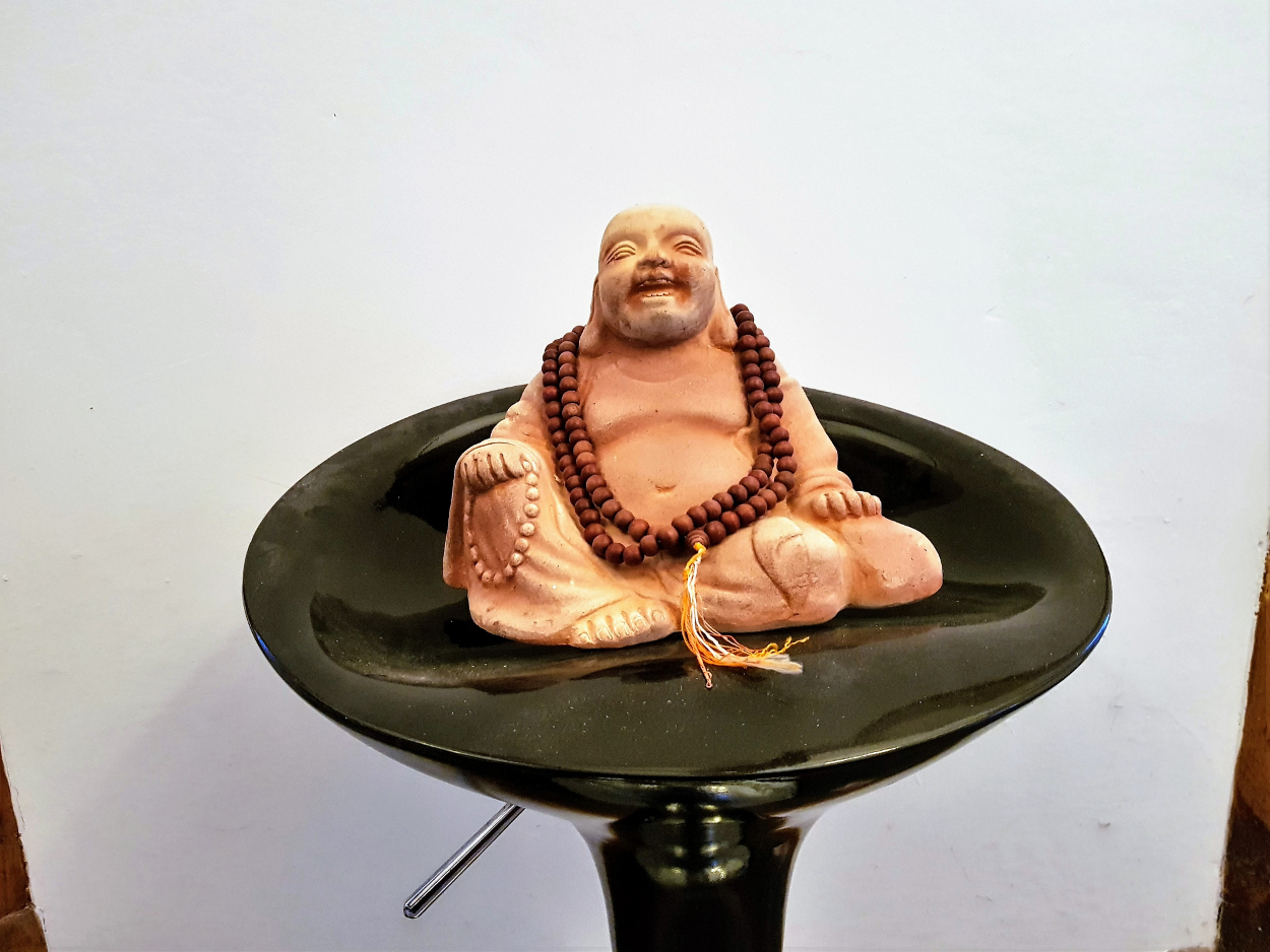 'Laughing Buddha' statue sitting on bar stool.