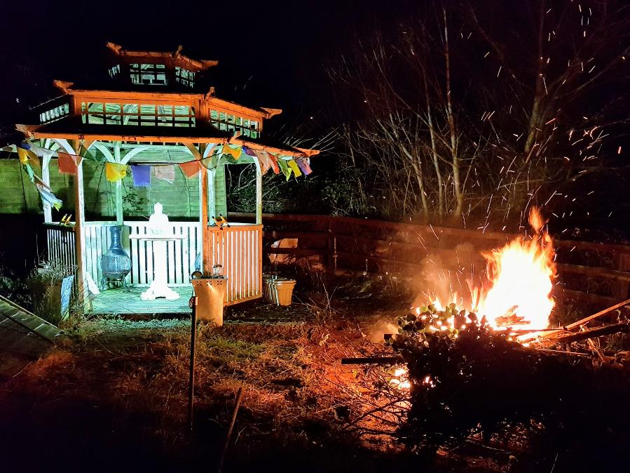 Blazing bonfire lighting up garden pagoda and Buddha statue