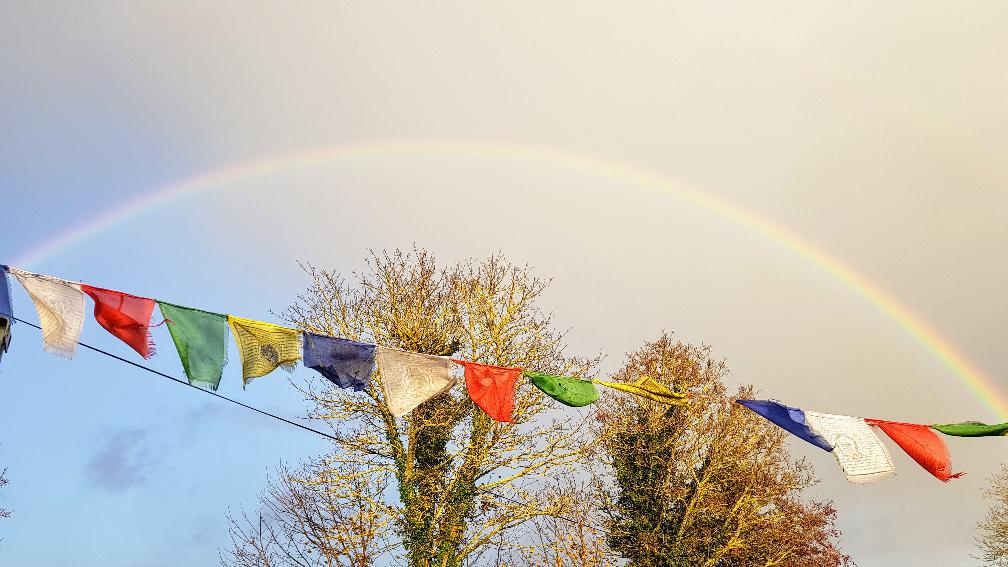 Rainbow in the sky above Prayer Flags