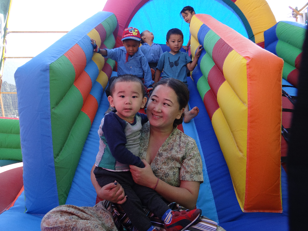 Mother smiling and holding small child at bottom of slide.