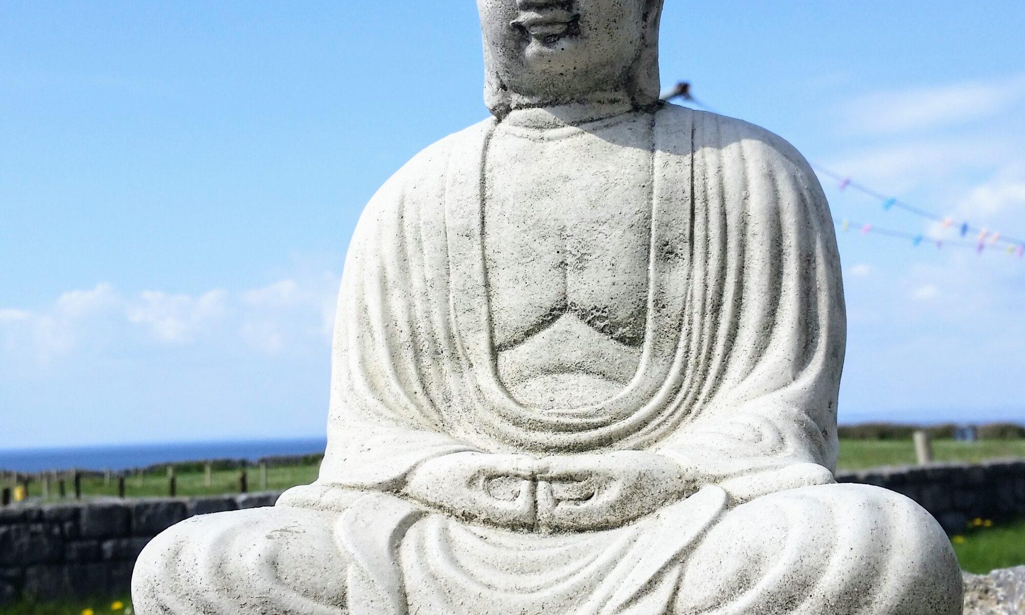 Buddha statue sitting on wall near beach and sea.