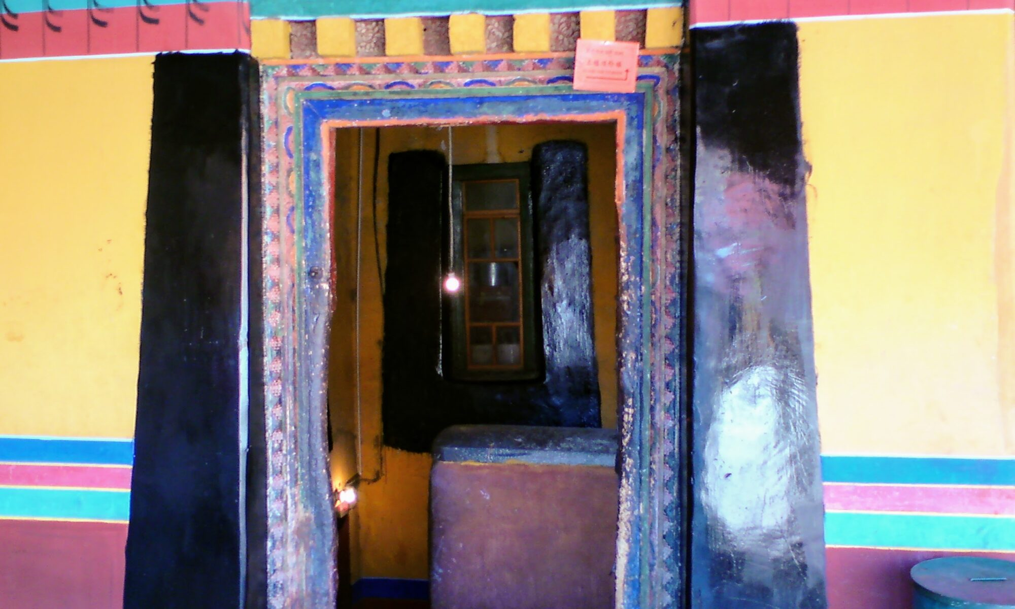 Open doorway revealing bare lightbulb hanging from the ceiling (Jokhang Temple, Lhasa, Tibet)