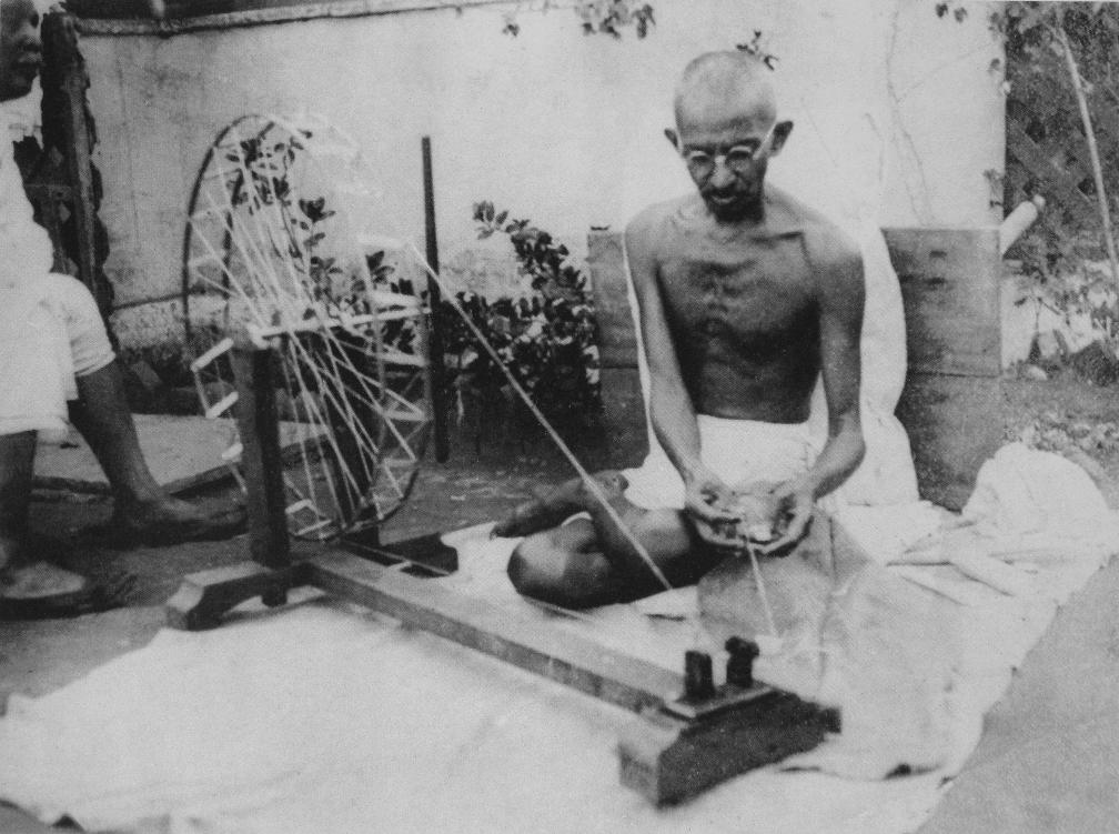 Mahatma Gandhi spinning yarn on a charkha. Location unknown.