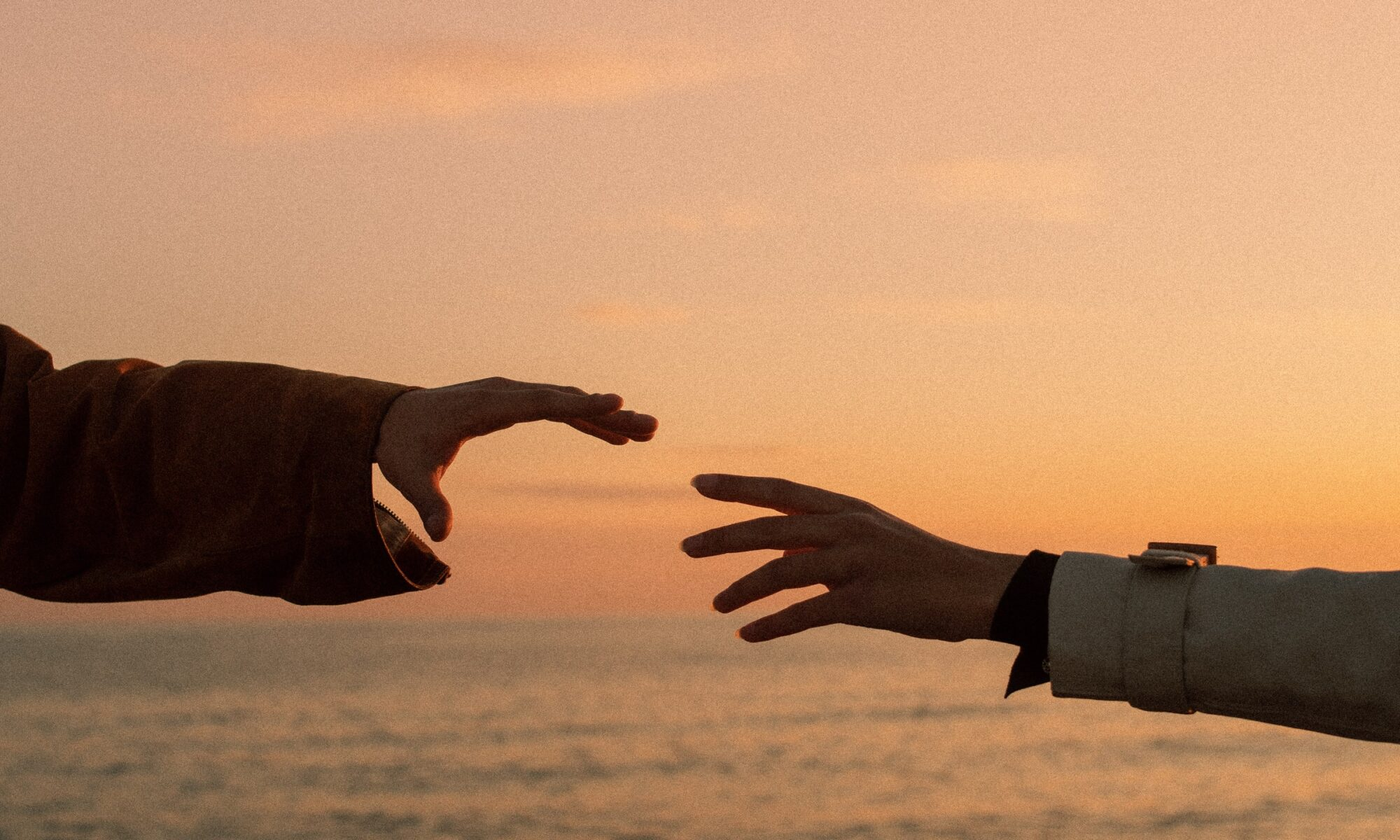 Two hands reaching out to touch each other.