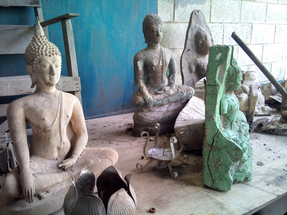 Perfect and imperfect Buddha statues on a wooden table